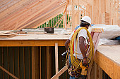 Carpenter moving tools down ladder at end of day to go home