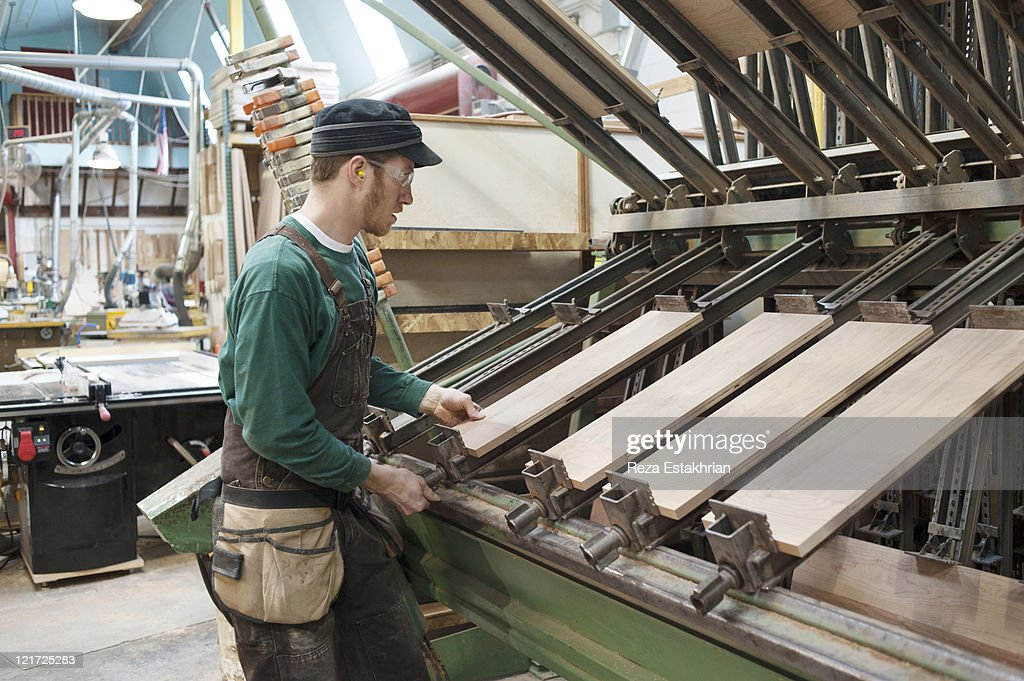 Carpenter places wood panels in joining machine : Stock Photo