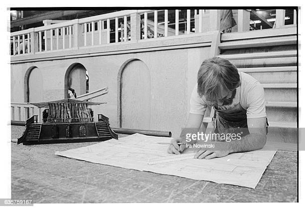 A carpenter reads a blue print The blue print is for the construction of the stage set for the opera La Gioconda Composer Amilcare Ponchielli
