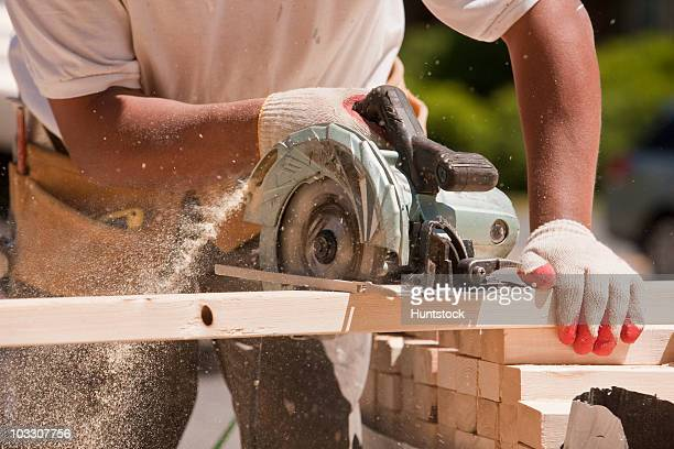 Carpenter sawing wall studs at a construction site