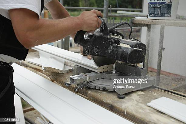 A carpenter sawing wood on a construction site on August 17 2010 in Berlin Germany The German stateowned development bank KfW Group sees a slight...