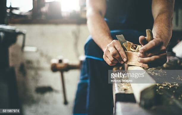 carpenter scraping wood with planer