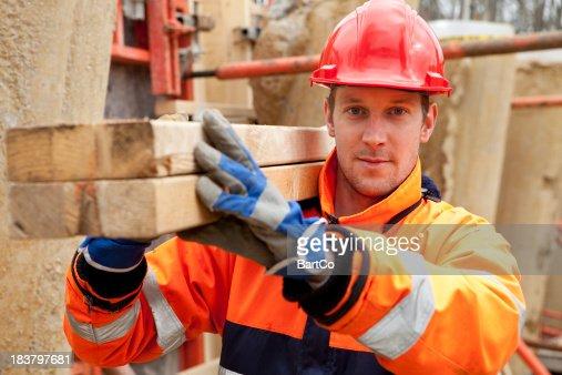 Carpenter smiling at construction site.