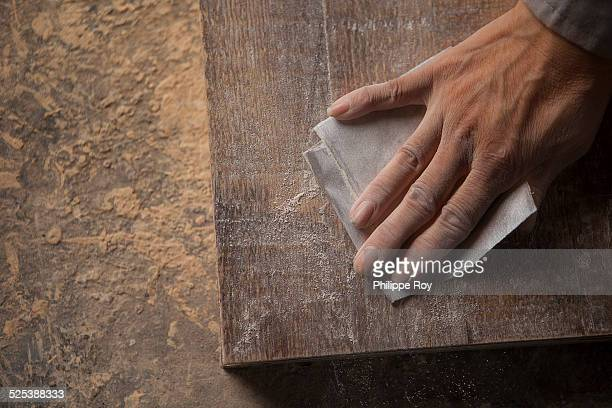 Carpenter smoothing surface of wood plank with sandpaper in factory, Jiangsu, China