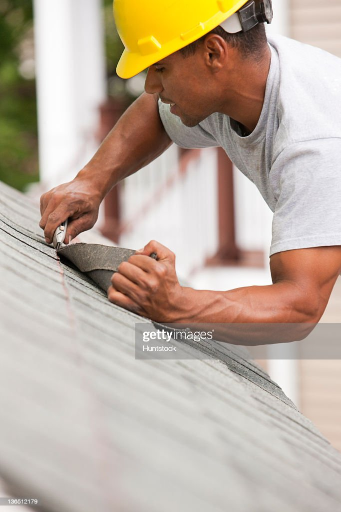 Carpenter trimming shingle at string line : Stock Photo