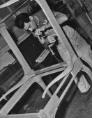 A carpenter using a brace and bit on a piece of furniture being made in the cabinet shop at the MGM film studios in Hollywood California circa 1950