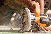 Carpenter using a circular saw at a construction site