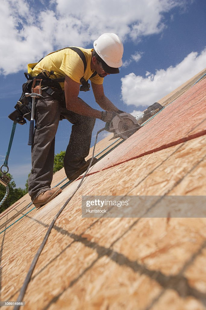 Carpenter using a circular saw on the roof panel at a house under construction site  & Carpenter Using A Circular Saw On The Roof Panel At A House Under ... memphite.com