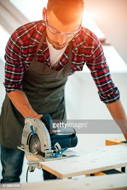 Carpentiere con sega circolare nel suo laboratorio.