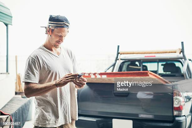 Carpenter using mobile phone by pick-up truck against clear sky