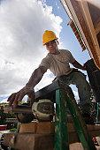 Carpenter using nail gun on the roof framing