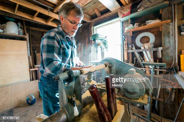 Carpenter, Woodworker working with electric lathe in his workshop