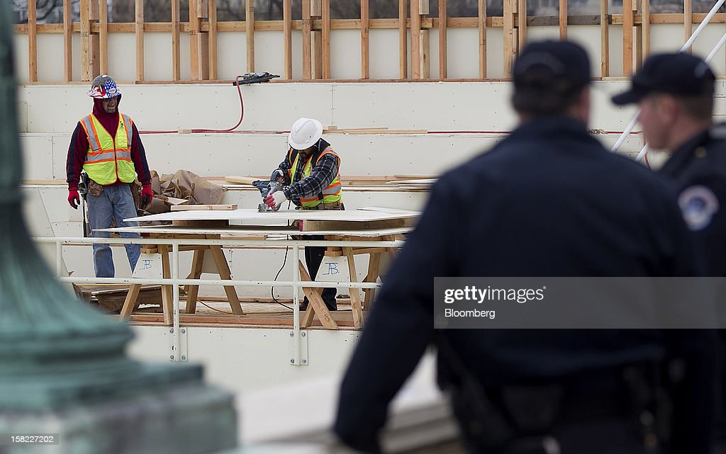 Carpenters are seen past police officers as they work on the construction of the platform being built on the west front of the U.S. Capitol in preparation for the inauguration ceremony of U.S. President Barack Obama in Washington, D.C., U.S., on Tuesday, Dec. 11, 2012. The presidential inauguration ceremony will take place on Jan. 21, 2013. Photographer: Andrew Harrer/Bloomberg via Getty Images
