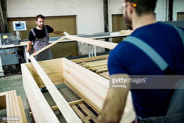 Carpenters carrying wood plank
