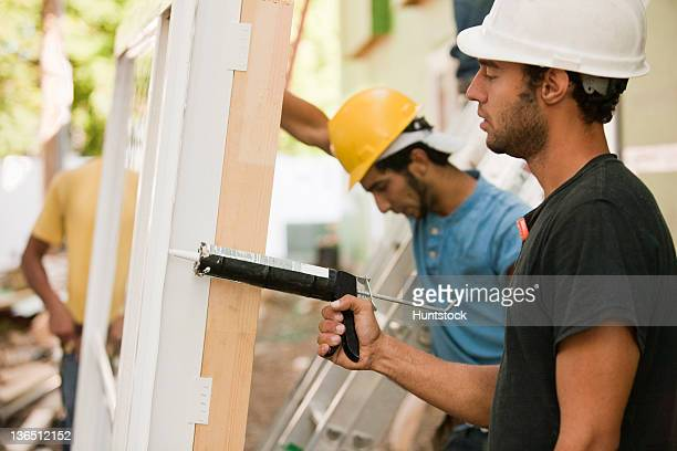 Carpenters caulking window frame prior to installation