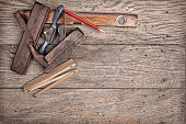 Different kinds of carpenterâ€'s hand tools like ruler, grater, water gage, meter and pencil are on a wooden background.
