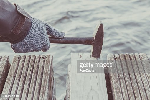 Carpenter's hands in the boards beating nails with an old. : Stock Photo