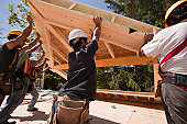Carpenters lifting roofing gable frame at a construction site