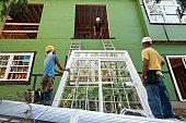 Carpenters preparing to hoist window frame to second floor