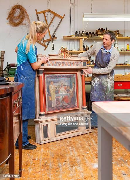Carpenters restoring antique art