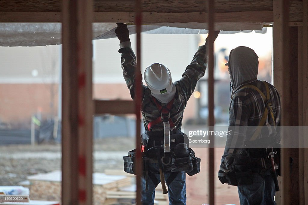 Carpenters work on a new Lexington Homes LLC townhome under construction in Des Plaines, Illinois, U.S., on Monday, Jan. 14, 2013. The U.S. Census Bureau is scheduled to release housing starts figures on Jan. 17. Photographer: Tim Boyle/Bloomberg via Getty Images