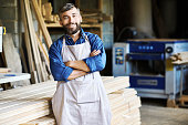 Portrait of mature bearded carpenter posing confidently with arms crossed standing in woodworking shop and smiling happily looking at camera