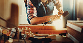 Closeup of unrecognizable early 30's man doing carpentry work in his garage. His scraping surface of a wooden plank by hitting a chisel with rubber hammer. Froont view, lit from side.