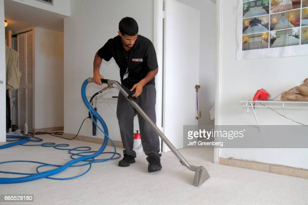 A carpet cleaner vacuuming the floor