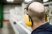 Carpet factory worker wearing sound-proof protective headphones