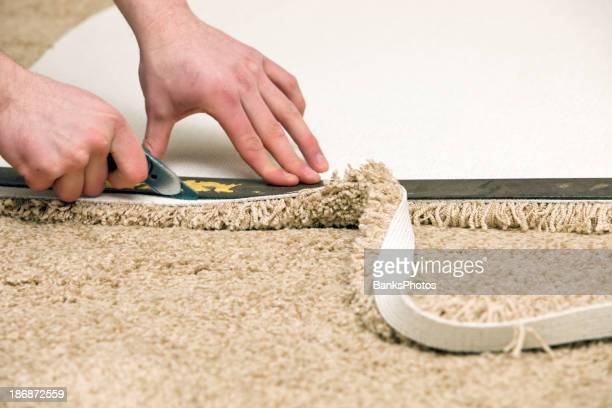 Carpet Installer Cutting with Knife and Straight Edge