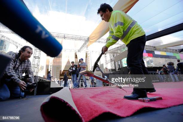 HOLLYWOOD CA FEBRUARY 22 2017 Carpet installer Rudy Morales from American Turf and Carpet uses stretching tools to position the red carpet in front...