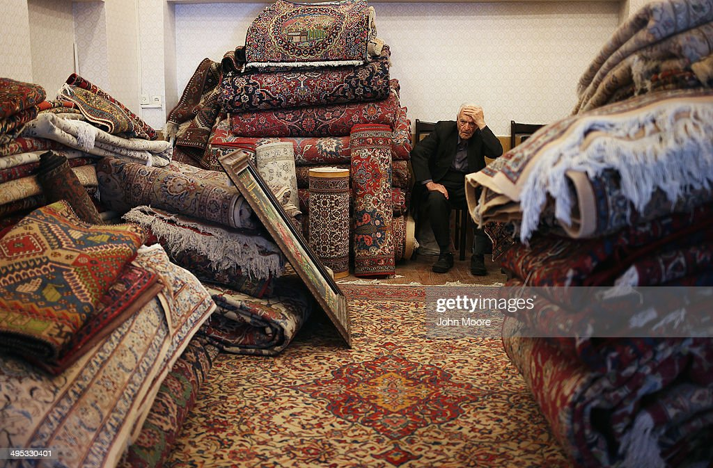A carpet vendor awaits customers at his shop in the Bazar-e Bozorg on June 2, 2014 in Isfahan, Iran. International sactions have severely affected Iran's carpet industry. Isfahan, with it's immense mosques, picturesque bridges and ancient historic bazaars, is a virtual living museum of Iranian traditional culture. It's also the Iran's top tourist destination for both Iranian and domestic visitors. On June 4 Iran marks the 25th anniversary of the death of the Ayatollah Khomeini and his legacy of the Islamic Revolution. In the background of the photo is the Imam Mosque, known as the Shah Mosque before the revolution.