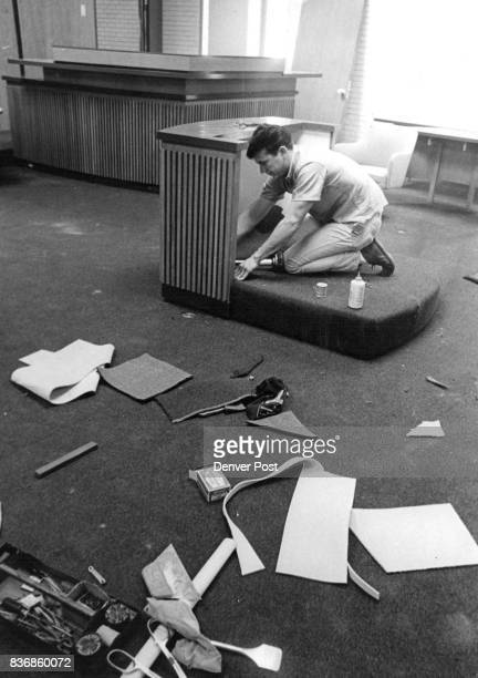 Carpetlayer Albert Pollard of 156 S Lincoln St uses a 'knee kicker' to stretch plush carpeting on a witness stand in a district courtroomThe modern...