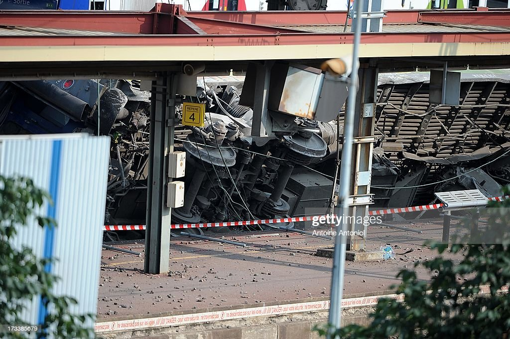 Carriages derailed in an accident lie within Bretigny-sur-Orge railway station on July 13, 2013 in Bretigny-sur-Orge, France. An intercity train carrying 385 passengers, travelling from Paris towards Limoges, derailed crashing into a station platform leaving six people dead and a further 30 injured on July 12, 2013. French investigators for SNCF have stated that the cause by a fault in the tracks.