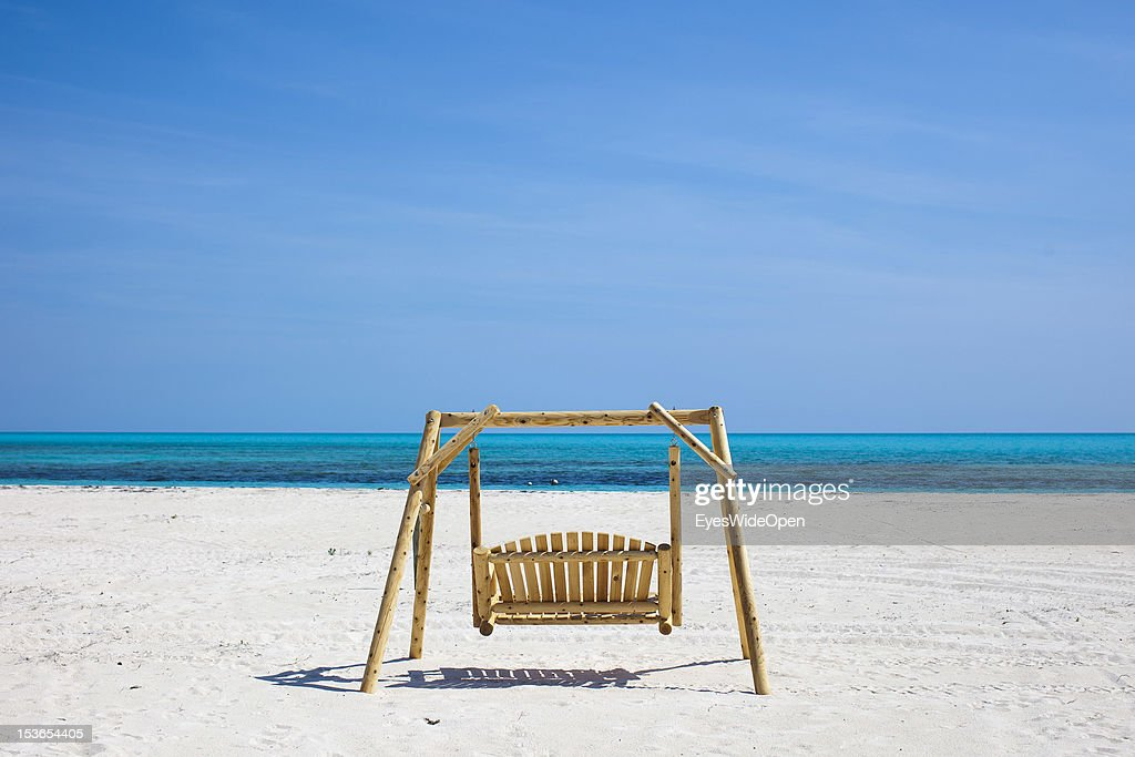 Carribean feeling - a lonely hollywood swing in the white sands of Shannas Cove Beach and the carribean sea on June 15, 2012 in Cat Island, The Bahamas.