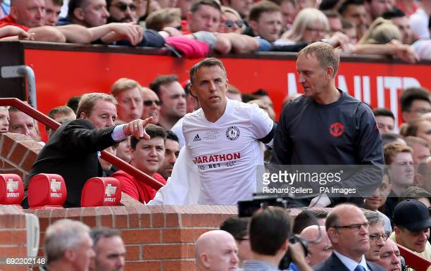 Carrick All Stars manager Harry Redknapp gives instructions to Phil Neville in the dugout during Michael Carrick's Testimonial match at Old Trafford...