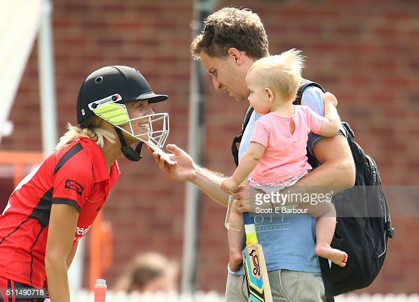 Carrie Bickmore walks out to bat as her partner Chris Walker holds their daughter Evie during the Medibank Melbourne Celebrity Twenty20 match at...