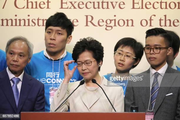 Carrie Lam Hong Kong's chief executiveelect center adjusts her glasses as her husband Lam Siupor left and son Lam Jitsi right look on during a news...