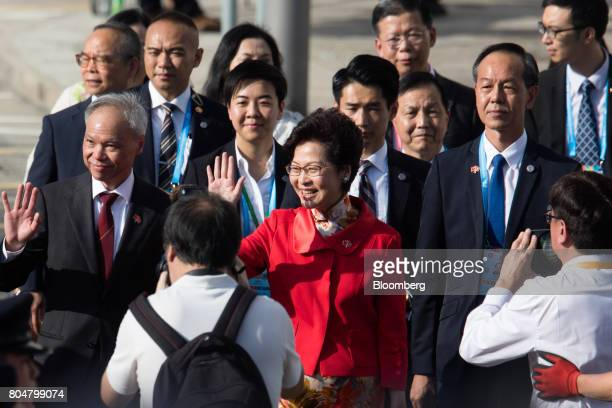 Carrie Lam Hong Kong's chief executiveelect center and her husband Lam Siupor left wave to attendees not pictured ahead of a flagraising ceremony at...