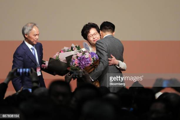 Carrie Lam Hong Kong's chief executiveelect center holding bouquet of flowers hug his son Lam Jitsi as her husband Lam Siupor looks on following the...