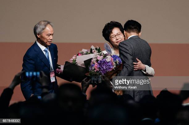 Carrie Lam Hong Kong's chief executiveelect center holding bouquet of flowers hug his son Jeremy Lam as her husband Lam Siupor looks after the...