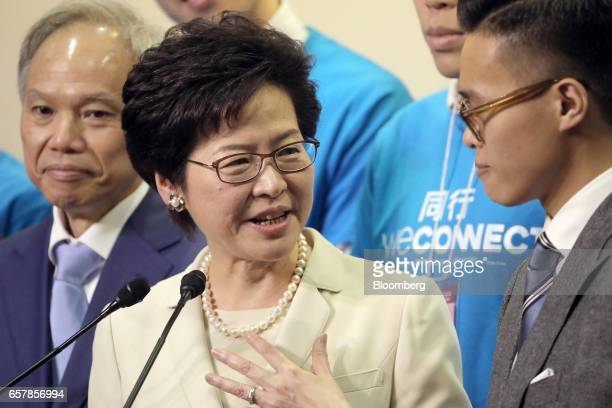 Carrie Lam Hong Kong's chief executiveelect speaks as her husband Lam Siupor left and son Lam Jitsi right look on during a news conference following...