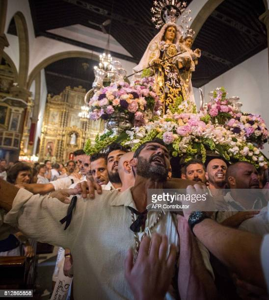 Carriers of the Great God Power brotherhood unload the Virgen del Carmen statue after its arrival on July 11 2017 at Puerto de la Cruz dock on the...