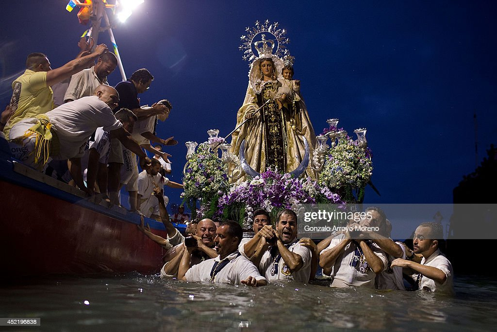 Carriers of the Great God Power brotherhood unload Virgen del Carmen statue after its journey on July 15, 2014 at Puerto de la Cruz dock on the Canary island of Tenerife, Spain. Since 1921, the statue of the Virgen del Carmen, patron saint of fishermen, has been carried with great fanfare annually as part of July Festivities to the Puerto de la Cruz dock where, at the end of its procession, it is hoisted aboard a decorated boat. Weather permitting, the boat carrying the statue, accompanied by a flotilla of other boats, makes a short journey along the island coast before returning to the harbour. In recent years, attendance at the event has numbered more than 35,000 people.