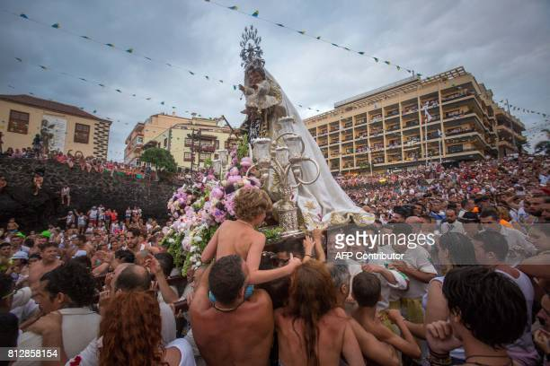 Carriers of the Great God Power brotherhood unload Virgin del Carmen statue after its journey on July 11 2017 at Puerto de la Cruz dock on the Canary...