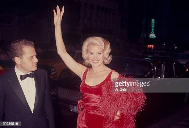 Carroll Baker with her husband Jack Garfein on the street She is waving wearing a red dress and feather boa limousine in the background circa 1960...