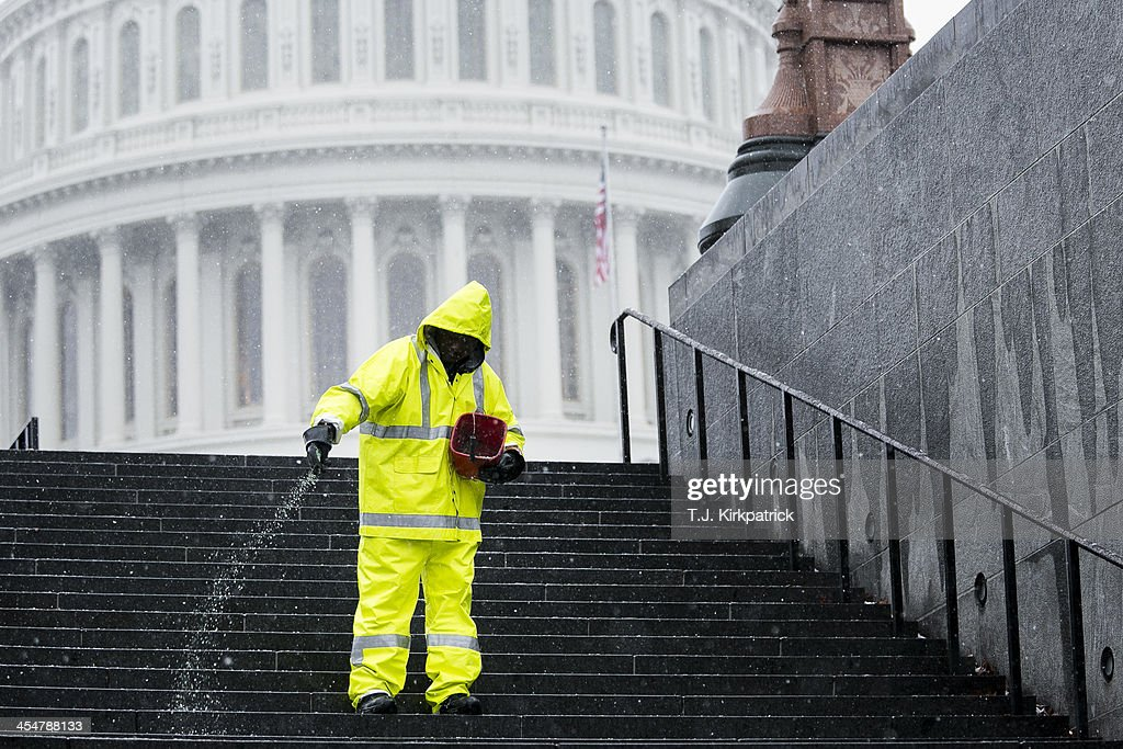 Carroll Rodgers, a stonemason with the Architect of the Capitol, salts steps outside the U.S. Capitol building on December 10, 2013 in Washington, DC. A winter storm that closed many federal government operations is expected to leave 3-5 inches of snow across the region.