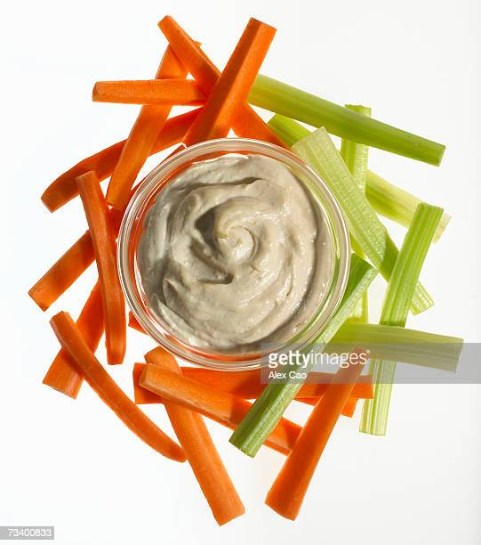 Carrot and celery sticks and bowl of hummus dip