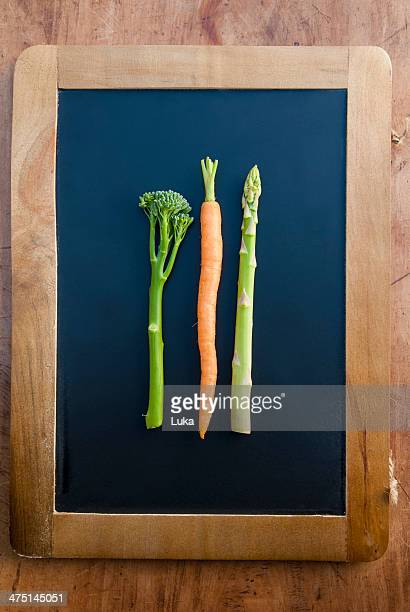 Carrot, broccoli and asparagus on blackboard, still life
