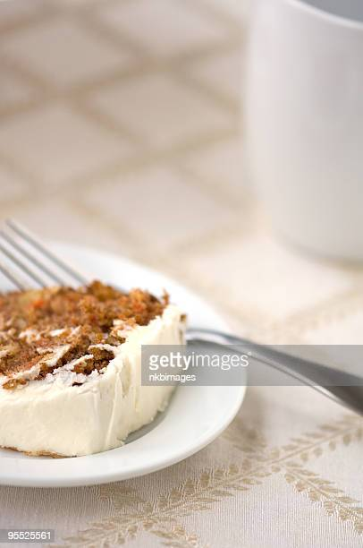 Carrot cake slice on plate with fork and coffee